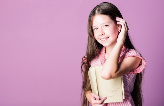 ホームスクーリング。ここに秘密を守ってください。書店のコンセプト。児童文学。本好き。家庭教育。幸せな子供時代。女の子のための小説。スペースをコピーします。小さな女の子が面白い話を読んだ。フィクションの本。