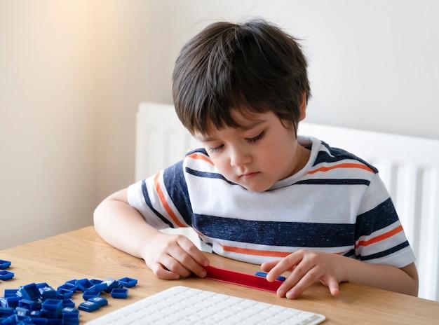 Ребенок дошкольного возраста, играющий в английскую игру слов, мальчик ребенка, сконцентрированный с правописанием английского письма с родителем дома. деятельность для детей, чтобы играть и учиться, концепция образования и homeschooling