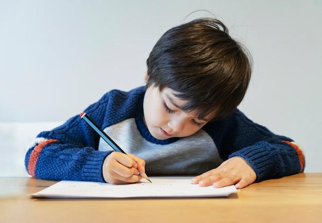 Портрет школьника мальчик, размещения на столе, делать домашнее задание, счастливый ребенок держит карандашом написание, мальчик, рисование на белой бумаге за столом, начальная школа и homeschooling концепция