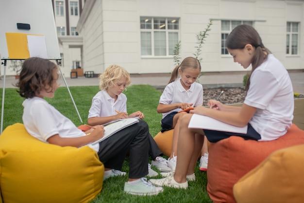 Домашнее задание. дети сидят вместе на стульях-мешках и делают домашнее задание