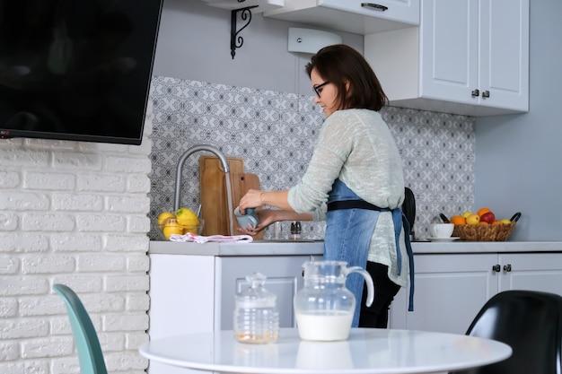 Домашнее задание на кухне, женщина-домохозяйка в фартуке моет чашку, грязную посуду