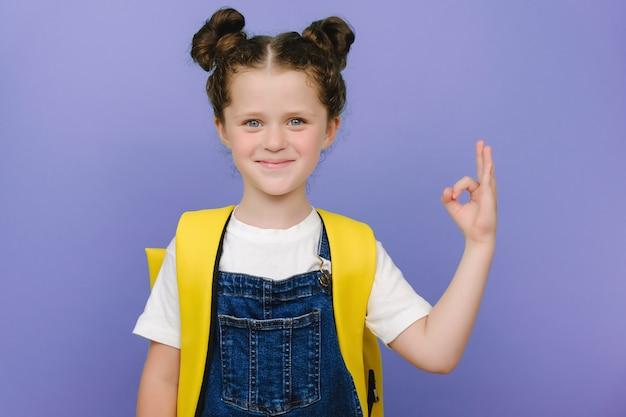 Домашнее задание - это просто! портрет сладкой милой школьницы, показывающей знак ок рука, носит желтый рюкзак, счастливый глядя на камеру, позирует изолированным на фиолетовом фоне. ребенок рекомендует лучший выбор образования