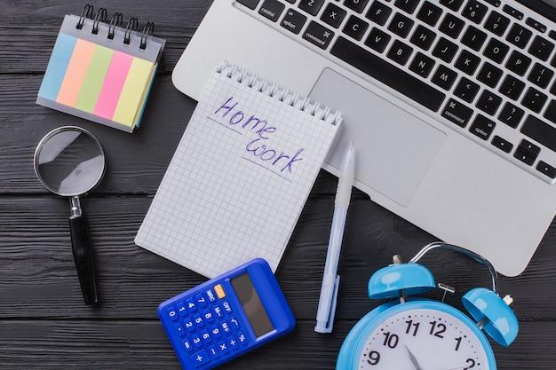 Плоские предметы домашнего задания. блокнот с ноутбуком и калькулятором на черном дереве.