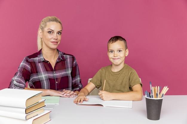 検疫の概念で一緒に宿題。本を持って机に座って勉強している子供を持つ母親。