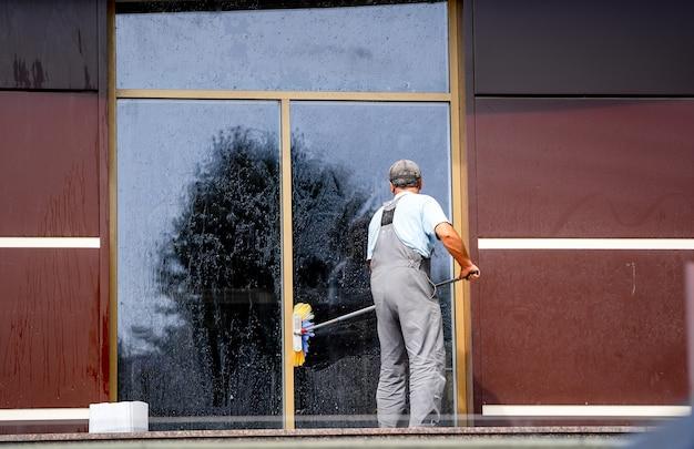 야외에서 걸레 세척 창을 가진 가사도우미. 전문 청소. 큰 파노라마 창.