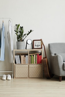 Homey apartment interior, focus on small bookstand with decor items and plant