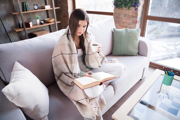 家庭的な女性は小説の本を読むソファで覆われた暖かい毛布をリビングルームでコーヒーを飲む