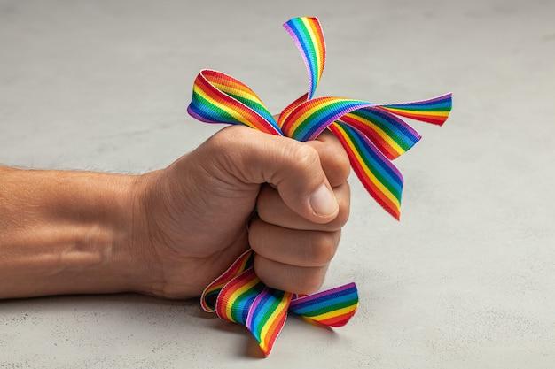 동성애 공포증. lgbt 프라이드를 중지하십시오. 남자는 손에 무지개 lgbt 리본을 쥐고 있습니다.