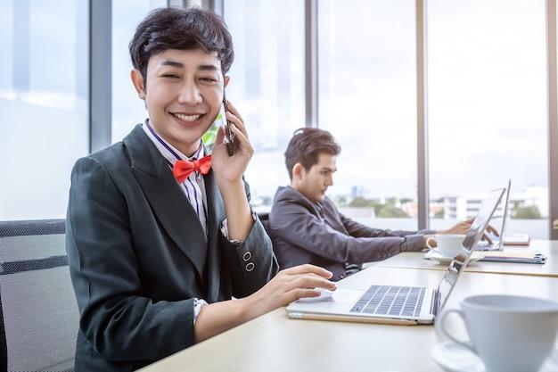 現代のオフィスの会議室でラップトップコンピューターとビジネスマングループで働いている間携帯電話で話している同性愛のアジアのビジネスマンlgbt