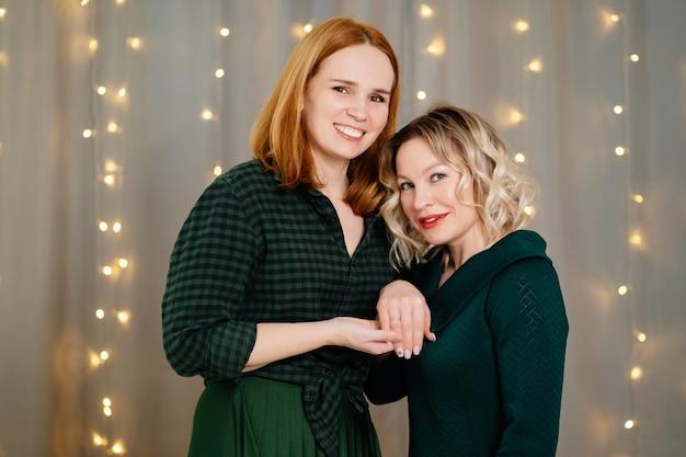 同性愛者のカップル。女性がプロポーズし、友達に指輪をつけて見せます。 lgbtの関係。レズビアンは家族を作り、結婚式を計画します。バレンタイン・デー