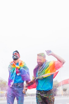 Homosexual couple in colorful powder having fun on parade