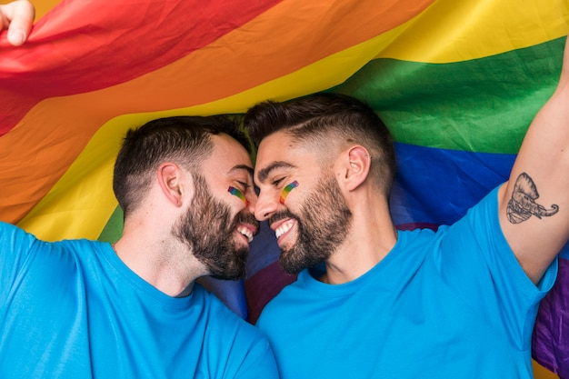 Homosexual couple gently cuddling on rainbow flag