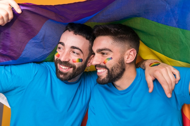 Homosexual couple of men hugging on lgbt flag