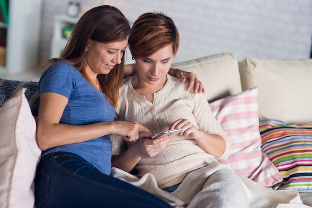 Гомосексуальная пара лесбиянок дома на диване смотрит смартфон, болтает в интернете и фотографирует