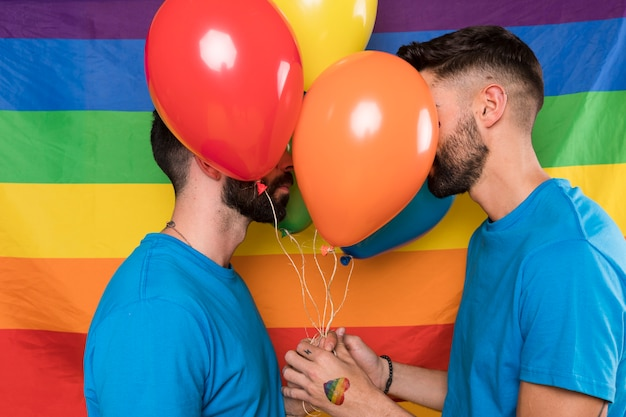 Homosexual couple with balloons on rainbow flag