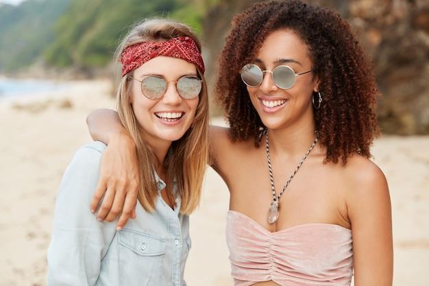 同性愛者の家族カップルは夏の休息を楽しみ、幸せな表情を持ち、山のあるビーチに立ち向かいながら抱き合います。人、友情、同性関係の概念
