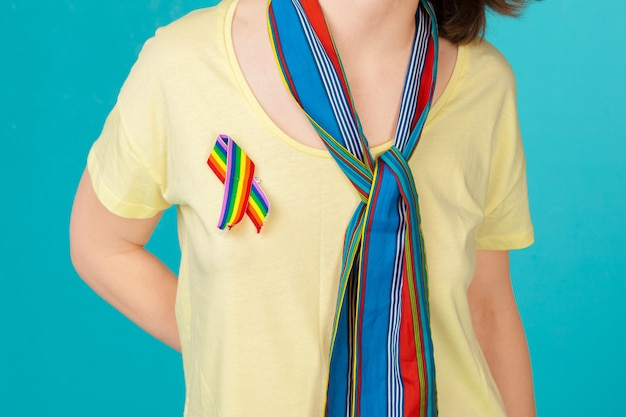 Homosexual and lgbt concept - close up of woman wearing gay pride awareness ribbon on her chest
