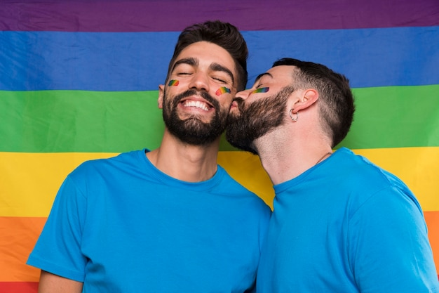 Homosexual man kissing boyfriend on lgbt flag