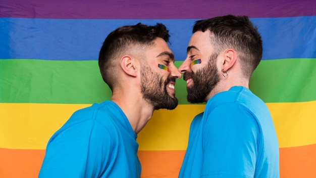 Homosexual men face to face on lgbt rainbow flag