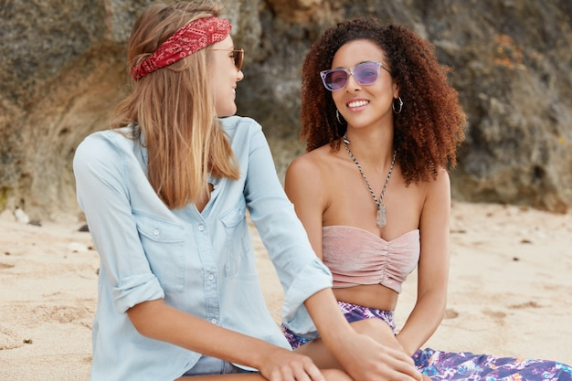 Le coppie omosessuali di razza mista hanno un appuntamento romantico all'aperto in spiaggia contro la scogliera, hanno una conversazione piacevole, indossano abiti alla moda e occhiali da sole, godono del resort in un paese caldo durante l'estate