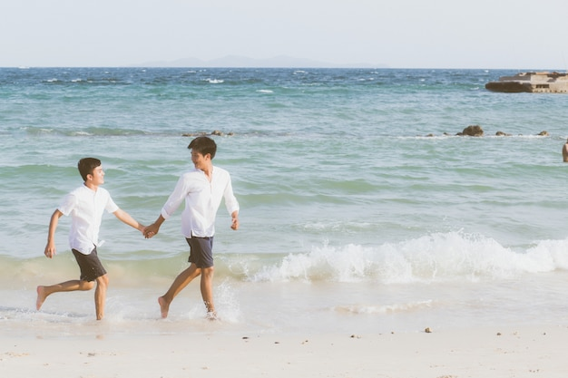 Homosexual portrait young asian couple running together on beach.