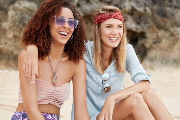 同性愛関係と愛の概念。女性のレズビアンはポジティブなルックスを持ち、お互いをハグし、美しい海の景色を眺めながら距離をのぞきます。ビーチで肯定的な若い女性が一体感を楽しむ