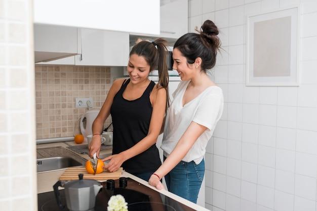 Homosexual women cooking in kitchen