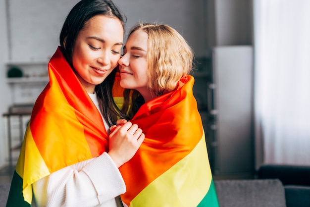 Homosexual women sweethearts wrapped in rainbow flag