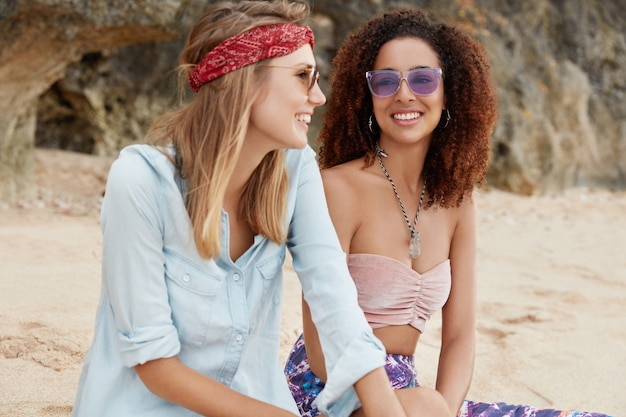 Homosexual young female couple have date near ocean, spend free time at coastline, have positive smiles, recreate together in hot country. people, same sex and relationships concept.