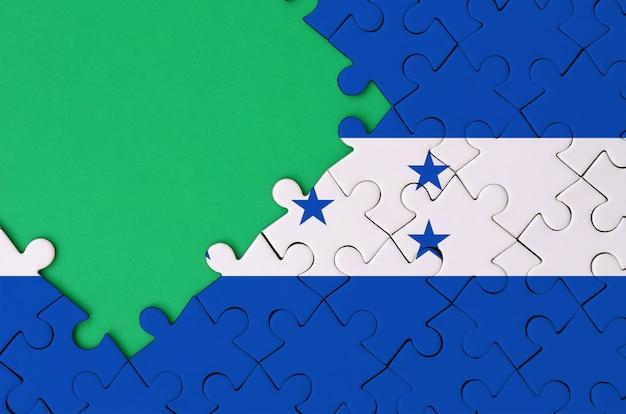 온두라스 국기는 왼쪽에 무료 녹색 복사 공간이있는 완성 된 직소 퍼즐에 그려져 있습니다.