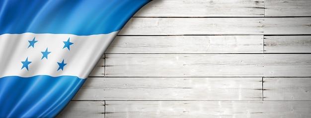 Флаг гондураса на старой белой стене. горизонтальный панорамный баннер.