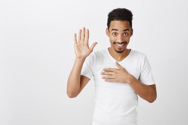 Честный и искренний красивый темнокожий парень дает обещание, держится за сердце и поднимает одну руку, ругается, говорит правду