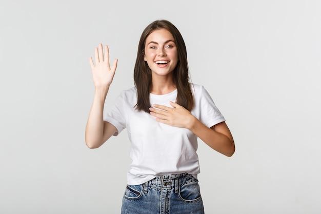 Честная улыбающаяся милая девушка говорит правду, поднимая руку, чтобы дать обещание.