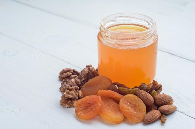 Мед, миндаль, грецкие орехи и курага. сушеные фрукты, лежа на белом деревянном столе.