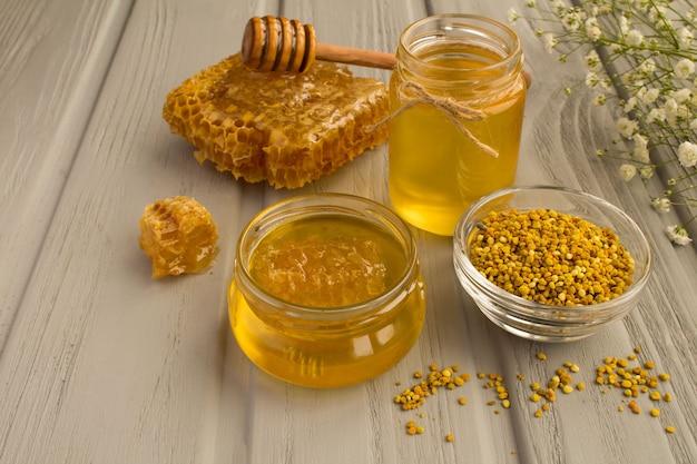 Мед и пчелиная пыльца на сером деревянном
