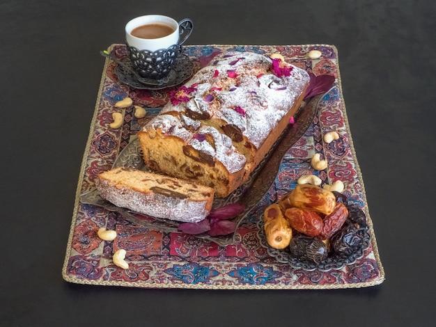 黒いテーブルに蜂蜜と日付のケーキ