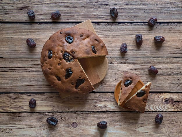 木製の表面に蜂蜜と日付ケーキ