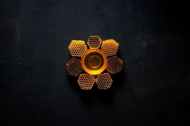 검은 탁자 위에 있는 꽃 모양의 꿀과 벌집, 위쪽 전망. 텍스트를 위한 공간입니다.