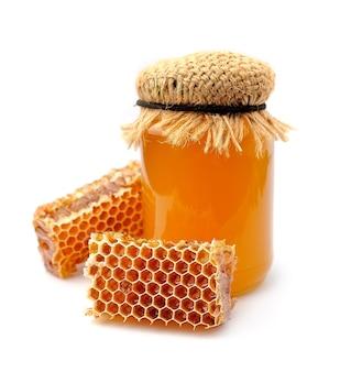 Мед и соты на белой стене.
