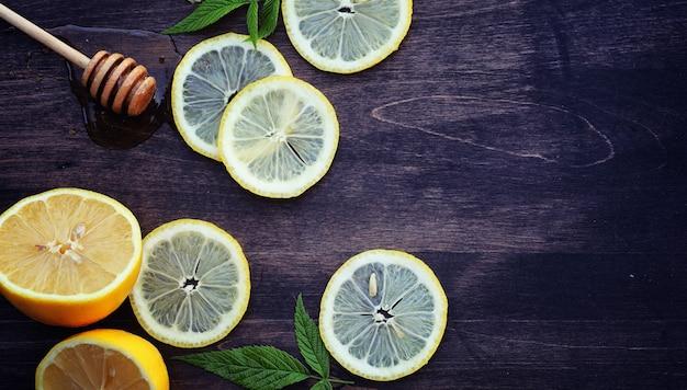 はちみつとレモン。ハニースティックとスライスしたレモンのスライスを木製のテーブルに。カップに入ったお茶と瓶に入ったスイートライムハニー。 Premium写真