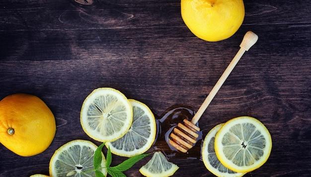 はちみつとレモン。ハニースティックとスライスしたレモンのスライスを木製のテーブルに。カップに入ったお茶と瓶に入ったスイートライムハニー。
