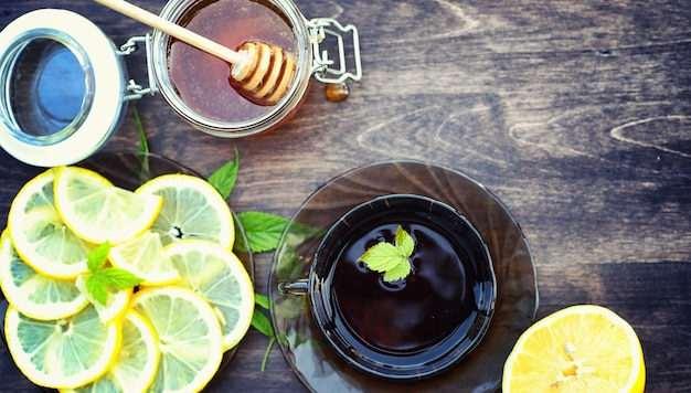 꿀과 레몬. 꿀 막대기와 나무 테이블에 얇게 썬 레몬 조각. 컵에 담긴 차와 항아리에 담긴 달콤한 라임 꿀.