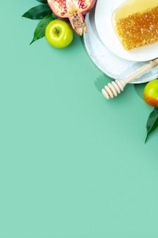 Мед, яблоко и гранат на мятно-зеленом фоне. концепция еврейский новый год с праздником рош ха-шана. креативное оформление традиционных символов. вид сверху. плоская планировка. скопируйте пространство. шана това.