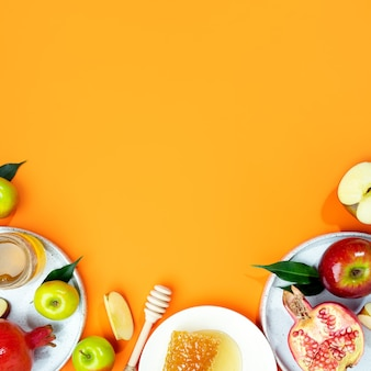 Мед, яблоко и гранат на оранжевом фоне. концепция еврейский новый год с праздником рош ха-шана. креативное оформление традиционных символов. вид сверху. плоская планировка. скопируйте пространство. шана това.