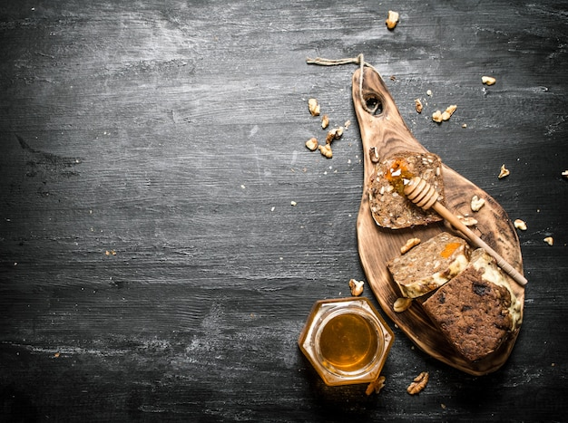 Honey background. fruit bread with natural honey and walnuts. on black rustic table.