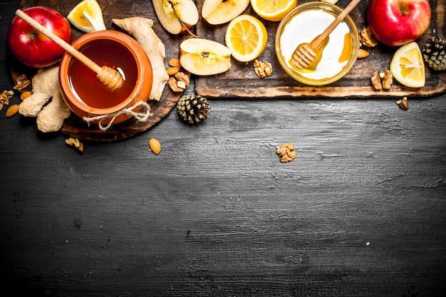 蜂蜜の背景。リンゴ、レモン、生姜、ナッツを入れた鍋に蜂蜜。黒い黒板に。