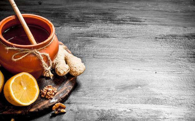蜂蜜の背景。生姜とレモンと鍋の蜂蜜。