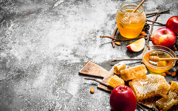 Медовый фон. мед с яблоками и орехами на деревенском столе.
