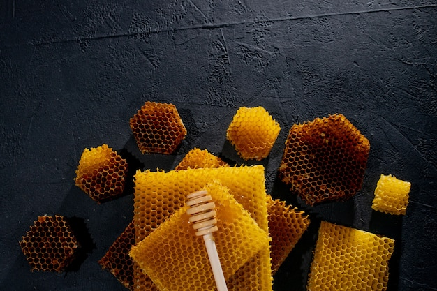꿀 배경입니다. 천연 벌집과 나무 숟가락. 검은 소박한 테이블에.