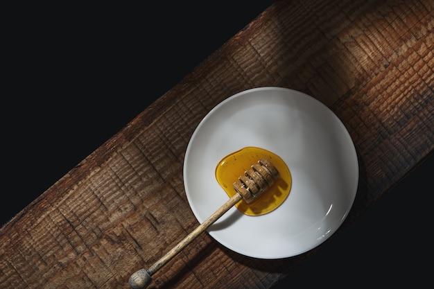 蜂蜜の背景。甘い蜂蜜とテーブルの上の蜂蜜のスプーン。上面図..